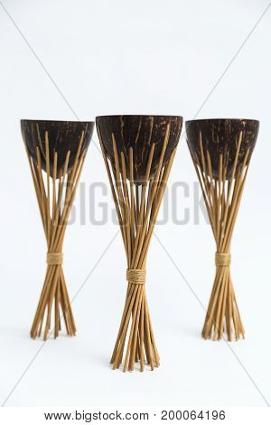 Old vintage exotic tropical eastern indian wooden three coconut torches with brach holders on white background.