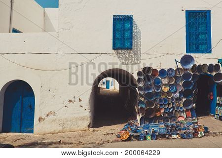 Colorful Moroccan faience pottery dishes on display in an alley outside in front of white house with blue door and windows