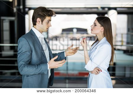 Cheerful Businesswoman Listening To Her Workmate Talking In Bright Office. Business Concept.