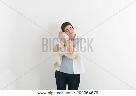 Childish young woman hugging soft plush cat with innocent smile and closed eyes. Sweet dreams