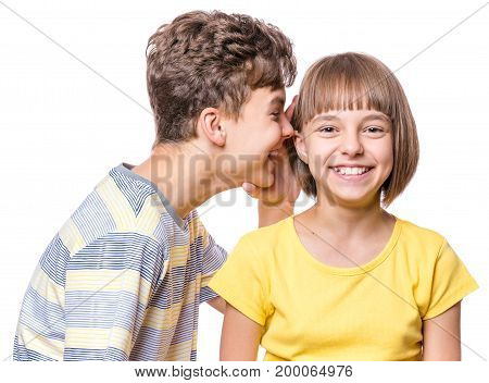 Friendship - teen boy whispering something to beautiful girl. Portrait of happy brother and sister, isolated on white background. Funny couple children - first love.