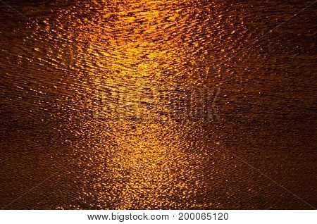 Liquid gold water surface texture at sunset on Ada lake in Belgrade, Serbia