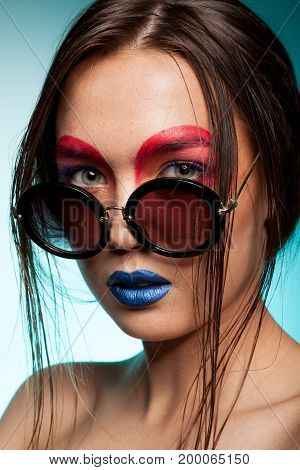 Gorgeous beautiful young model with creative make up, hairstyle and glasses Beauty and fashion. Artistic on stage make up