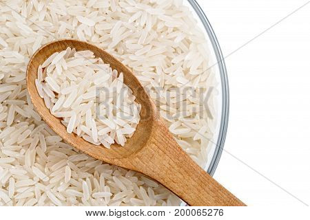 Healthy food. Close up of parboiled rice and wooden spoon in glass bowl isolated on white background. Top view. High resolution product.