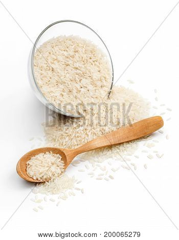 Glass bowl and wooden spoon with scattered rice on white background. Close up. High resolution product