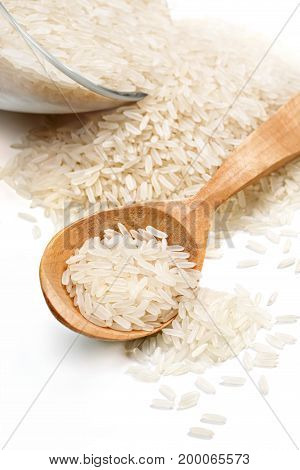 Close up of glass bowl and wooden spoon with scattered rice on white background. High resolution product.
