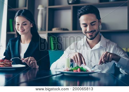 Lunch together. Two young cute lovers are sitting in a fancy restaurant wearing smart outfits and eating delicious salad and a dessert smiling.
