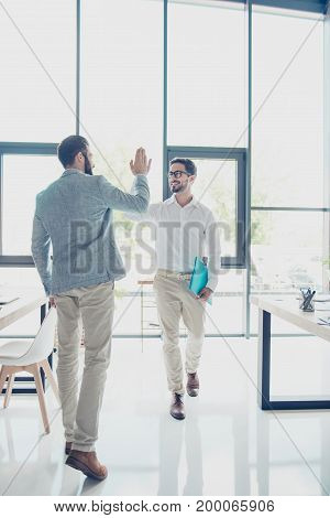 Full size of two handsome brunet guys colleagues dressed classy and elegant are giving high five while passing each other in office successful friendly men