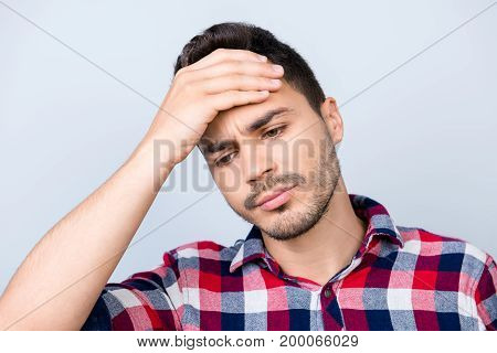 Tired Sick Handsome Young Brunet Man With Sad Grimace. He Is Holding The Forehead, Wearing The Check