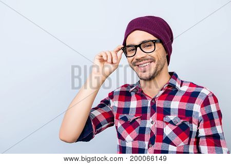 Dreamy Student Hipster In A Casual Checkered Shirt, Black Glasses, Hat, Smiling And Looking At The C