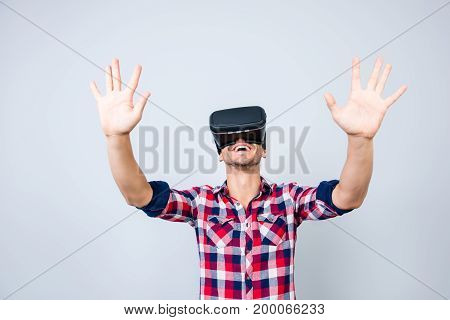 Excited Young Man Is Getting Experience Using Vr-headset Glasses Of Virtual Reality Gesticulating Wi