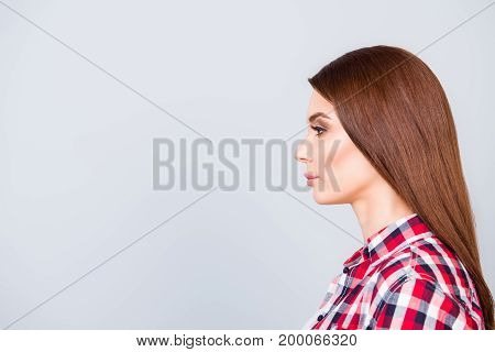 Side Profile Of Young Brown Haired Lady Student In Checkered Casual Shirt, Standing With Serious Gri