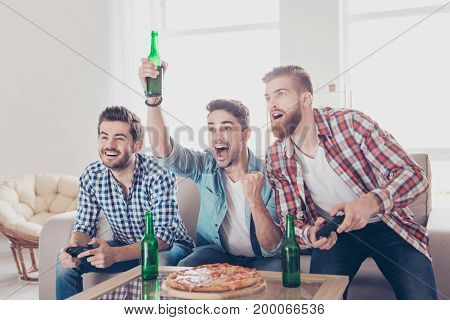 Crazy funky chill joy winners and looser! Three young men are sitting on couch and playing video games indoors at home with beer and pizza expressing emotions and feelings gesturing