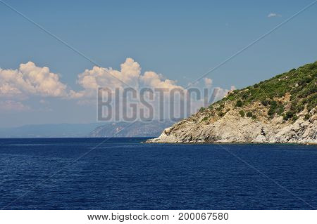 Athos peninsula, Greece. Steep edges of Athos peninsula. Blue sky with white clouds over the azure sea.