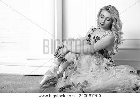 Young beautiful ballerina sitting on floor. Black and white photo