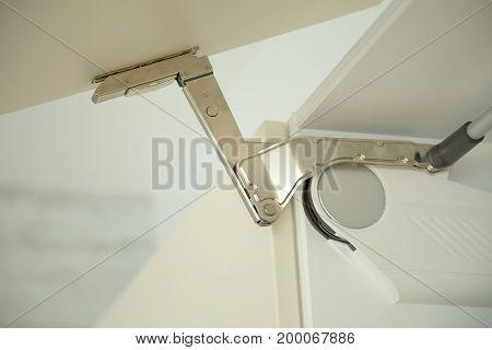 Detail of hinge on door of a kitchen cupboard .