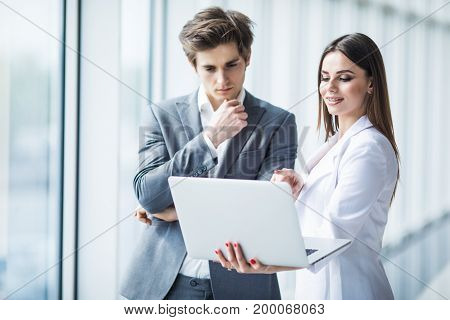Business Man And Business Woman Discussing New Project On The Laptop Atanding Against In Office Room