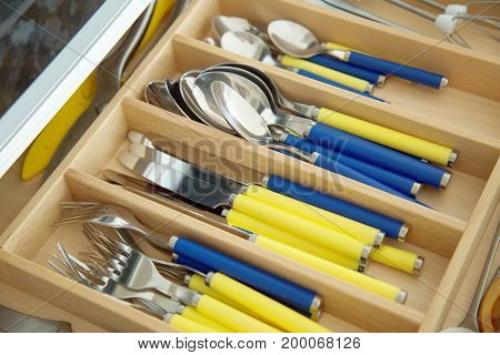 Spoons, forks and knifes in cutlery box drawer in kitchen cupboard