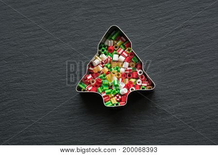 Christmas background. Handmade Beaded Ornaments Kids Can Make. Christmas themed cookie cutters on black. Holiday card.