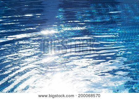 Patches of light of the sun on water in the pool