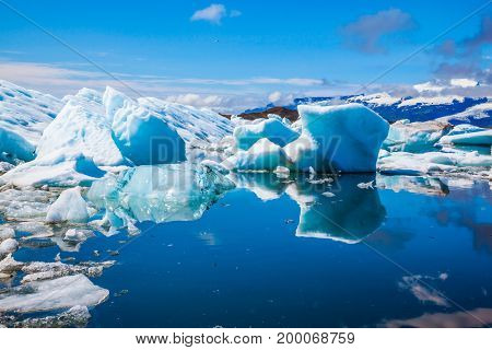 The unique nature of Iceland. Icebergs and ice floes are reflected in the smooth water surface. Drift ice Ice Lagoon - Jokulsarlon. The concept of extreme northern tourism