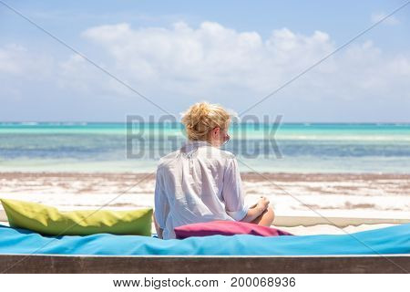 Relaxed woman in luxury lounger, reading book, enjoying summer vacations on beautiful beach. Lady feeling free, relaxed and happy. Concept of vacations, freedom, happiness, enjoyment and well being.