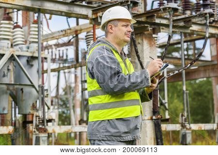 Electrician writing in electrical substation in autumn day