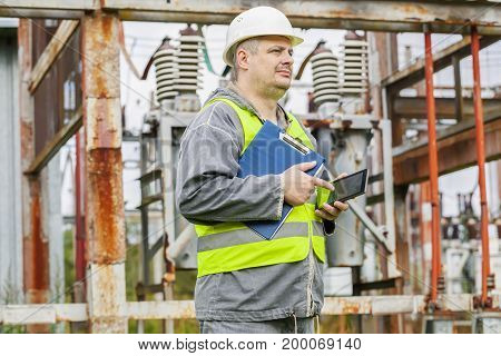 Electrician using tablet PC in electrical substation .