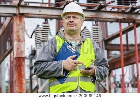Electrician using tablet PC and take substation technical inspection