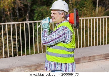 Road construction worker with traffic cone on the bridge