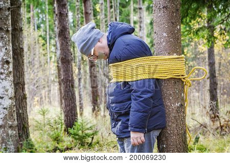 Hostage tied to the tree in autumn day