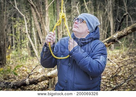 Depressed man near gallows noose in autumn day