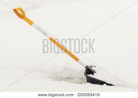 Snow shovel in snow in winter day
