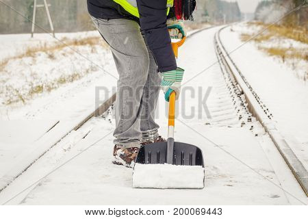 Railroad employee clean snow from the railway crossing