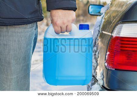 Man with car window washing fluid near car