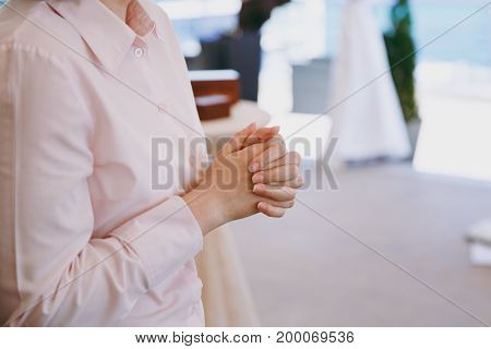 The folded fingers of a woman at a wedding