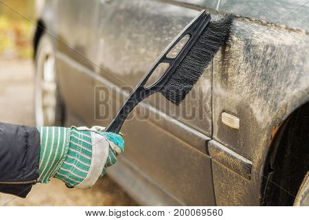 Man cleaning car in autumn day .