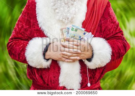 Santa Claus with euro banknotes and gift bag on green