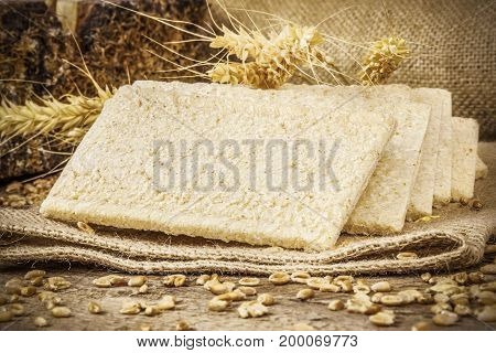 Crispbread with grains and ears in backgrounds