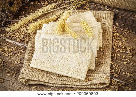Crispbread with grains and ears on wooden table