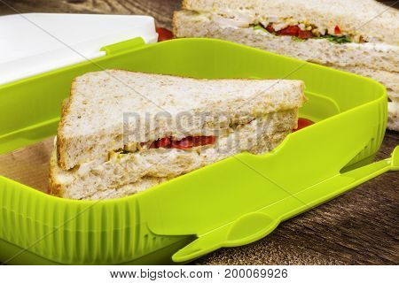 Chicken sandwiches in food box in room .