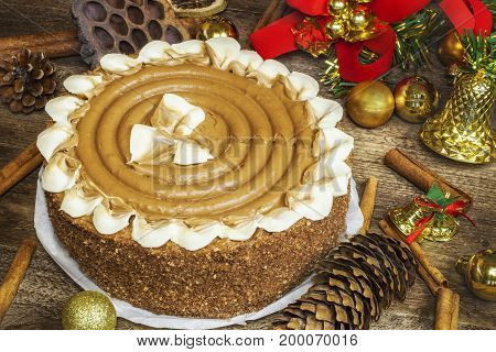 Chocolate cake on wooden table near Christmas decoration