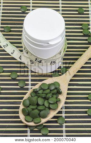 Spirulina,chlorella pills and measure tape around pill bottle