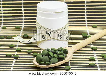 Spirulina,chlorella pills on wood spoon and measure tape around pill bottle