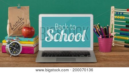 Digital composite of Computer on a school table with back to school text on screen