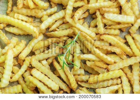 French fries with rosemary on paper .