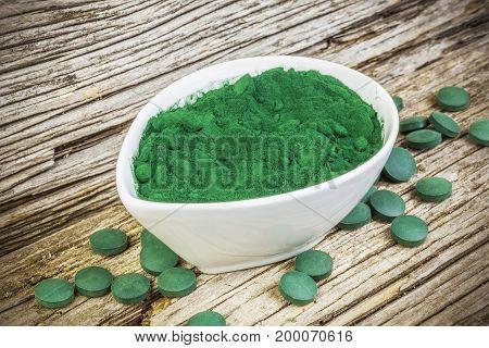Spirulina,chlorella supplement powder and pills on wood