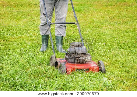 Landscaping worker pushing lawnmower on lawn .