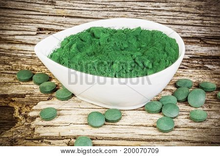 Spirulina,chlorella supplement powder and pills in white bowl and on wood