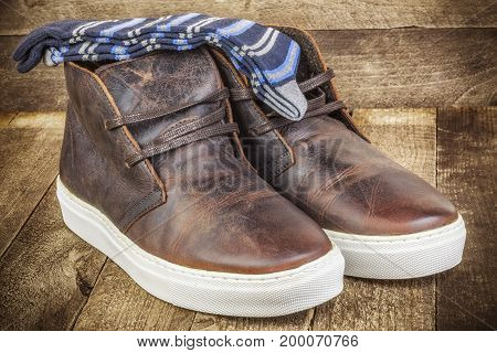 Desert boots with socks on wood .